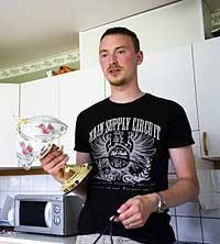 Erik Blohm visar lampa som drar ström när den avstängd.
